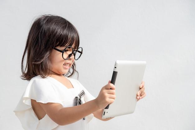 Zszokowana i zaskoczona mała dziewczynka w internecie z koncepcją cyfrowego tabletu dla zdumienia, zdumienia, popełnienia błędu, oszołomienia i zaniemienia lub zobaczenia czegoś, czego nie powinien widzieć