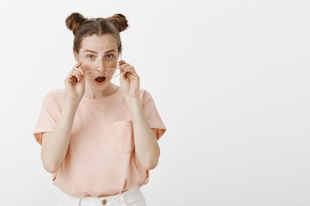 Zszokowana i zaskoczona ruda nastolatka pozuje pod białą ścianą