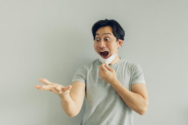 Zszokowana i zaskoczona twarz mężczyzny w białej higienicznej masce w szarym t-shircie.