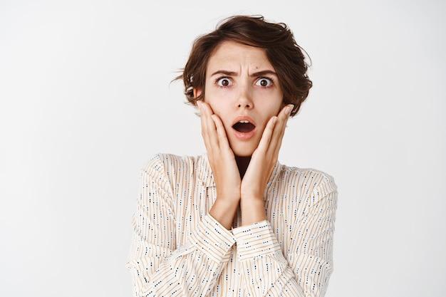 Zszokowana i zdezorientowana kobieta dotykająca zaniepokojonej twarzy i otwartych ust, marszcząca brwi, patrząc na katastrofę lub straszne wiadomości, stojąca na białej ścianie