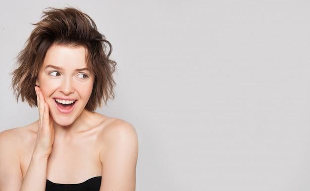 Zszokowana i zdziwiona dziewczyna uśmiecha się i patrzy w bok, przedstawiając twój produkt na białym tle szarej ścianie. naturalne piękno bez makijażu kobieta zadziwiała. wolne miejsce na tekst. ekspresyjny wyraz twarzy