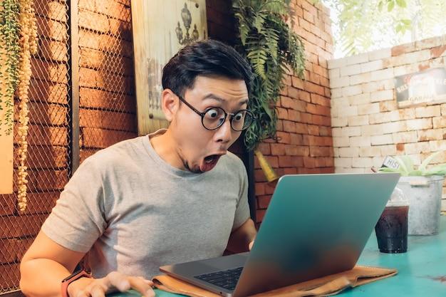 Zszokowana i zdziwiona twarz mężczyzny pracuje na swoim laptopie w kawiarni.