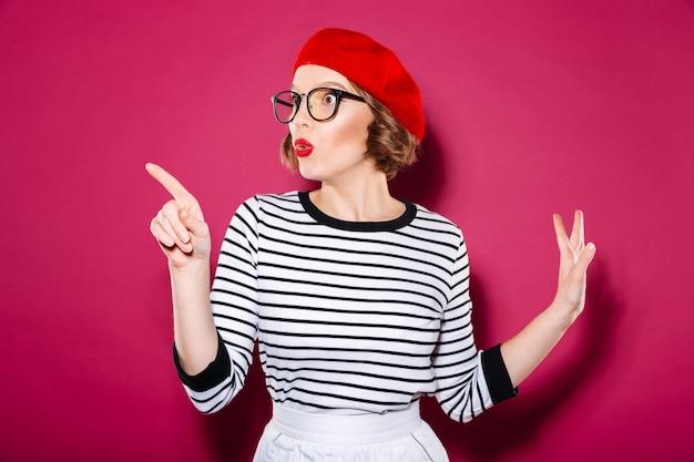 Zszokowana imbirowa kobieta w okularach wskazująca i odwracająca wzrok na różowo