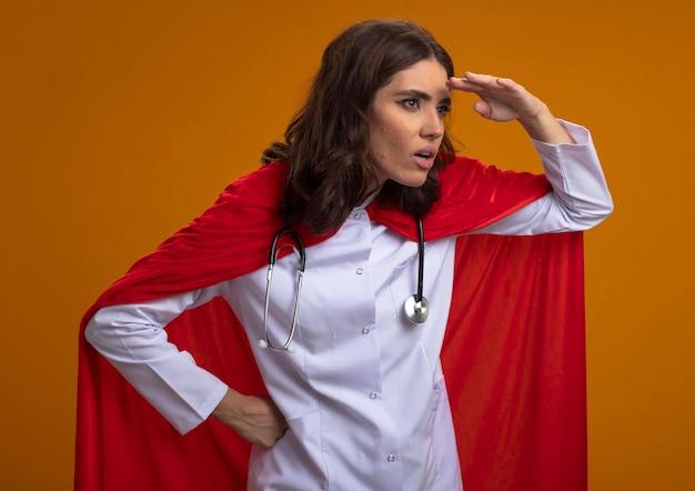 Zszokowana kaukaski dziewczyna superbohatera w mundurze lekarza z czerwoną peleryną i stetoskopem trzyma dłoń