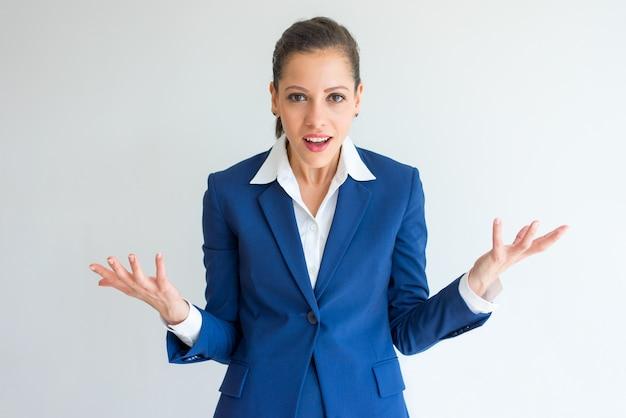 Zszokowana kobieta biznesu z pytaniem twarz rozprzestrzeniania się ręce.