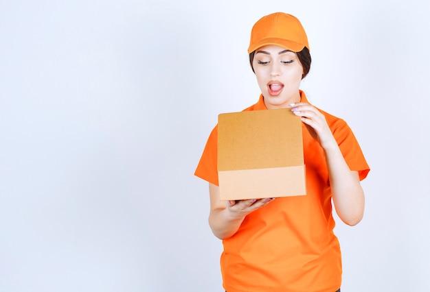 Zszokowana kobieta dostawy otwierająca paczkę