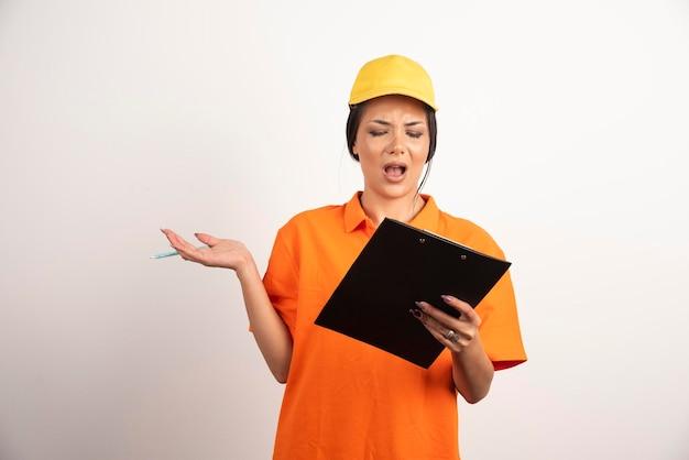 Zszokowana kobieta kurier z ołówkiem patrząc na schowek na białej ścianie.