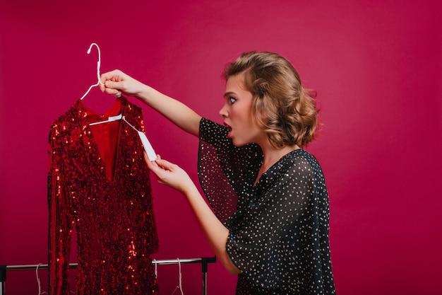 Zszokowana kobieta patrząc na cenę na błyszczącą czerwoną sukienkę w butiku. wewnątrz portret zdumiony, młoda modelka trzyma wieszak z drogim strojem.