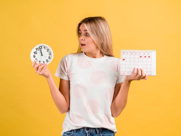 Zszokowana kobieta, patrząc na zegar