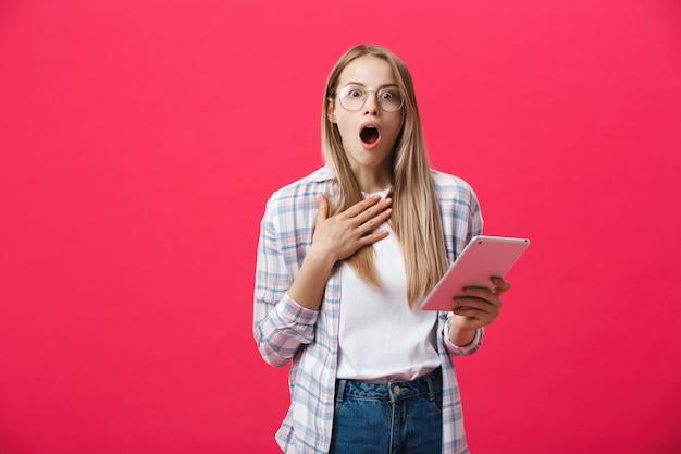 Zszokowana kobieta patrzeje cyfrową pastylkę z niespodzianką i szok nad różowym tłem. zdziwienie lub gorące wiadomości w internecie