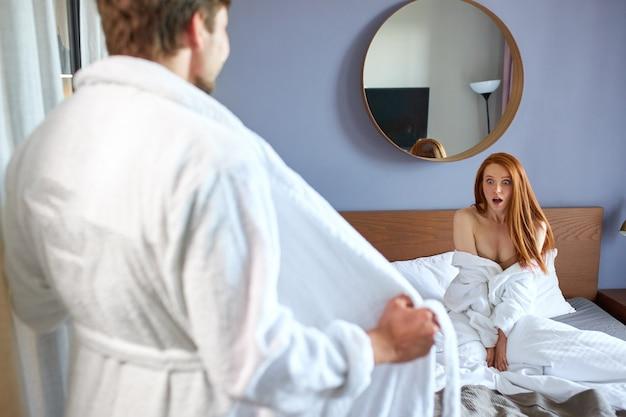 Zszokowana kobieta patrzy na mężczyznę bez koszuli