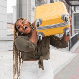 Zszokowana kobieta próbuje podnieść na ramieniu ciężki bagaż
