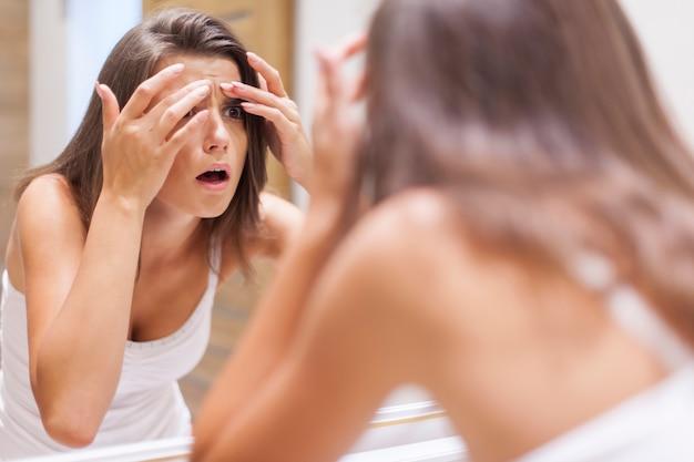 Zszokowana kobieta ściska pryszcz w łazience