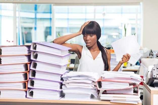 Zszokowana kobieta siedzi przy stole z wieloma papierami w biurze