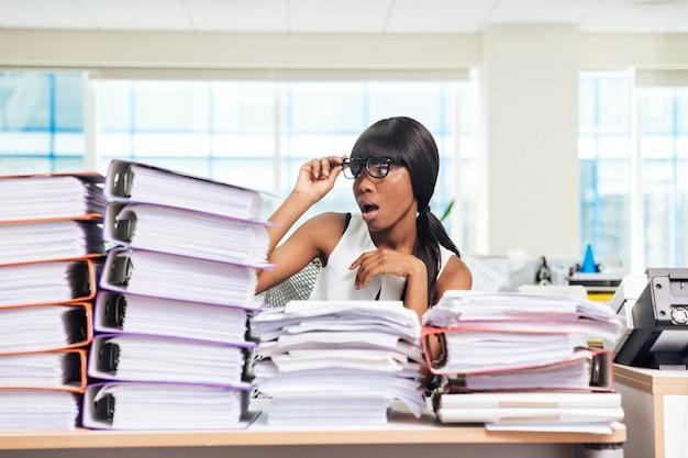 Zszokowana kobieta siedzi przy stole z wieloma pracami w biurze