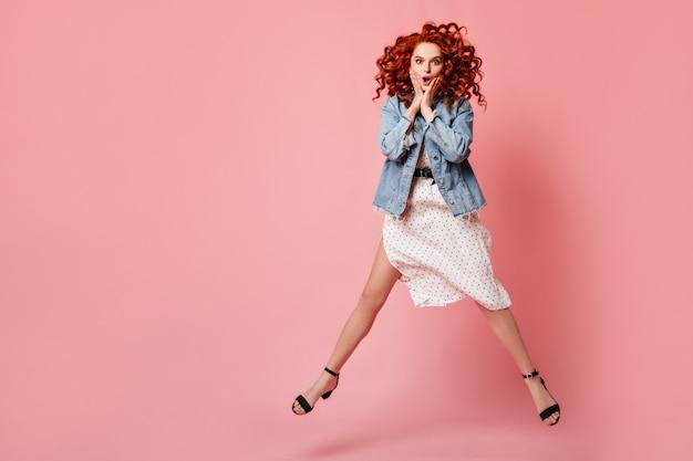 Zszokowana kobieta skacze na różowym tle z kręconymi fryzurami. imbirowa dziewczyna w dżinsowej kurtce i sukience, zabawy w studio.