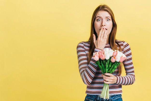Zszokowana kobieta trzyma bukiet tulipanów