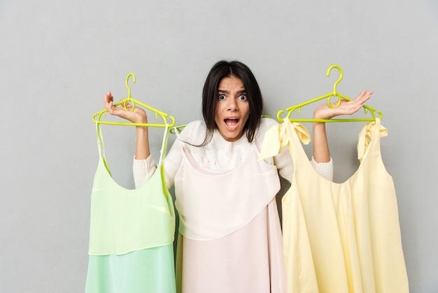 Zszokowana kobieta trzyma sukienki na wieszakach