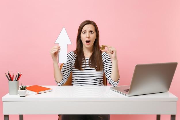 Zszokowana kobieta trzymająca w górę strzałkę i metalową monetę bitcoin o złotym kolorze przyszła waluta pracuje w biurze z laptopem na pc