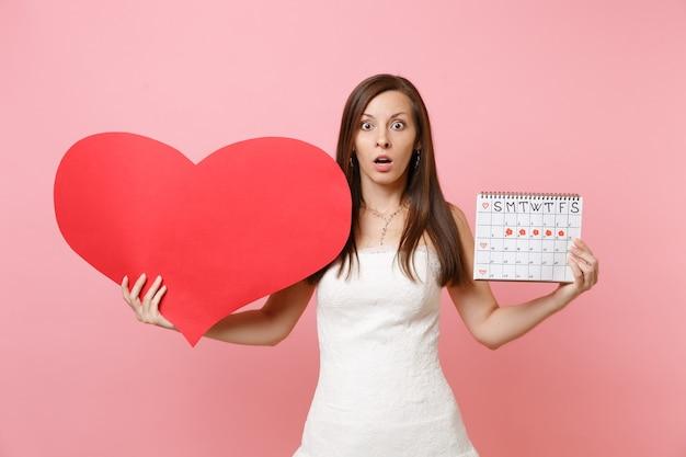 Zszokowana kobieta w białej sukni, trzymająca pusty pusty kalendarz kobiecych okresów z czerwonym sercem do sprawdzania dni menstruacyjnych