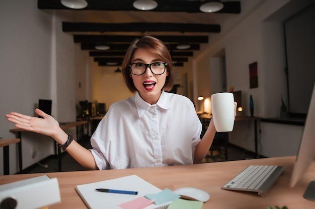 Zszokowana kobieta w biurze. patrząc w kamerę