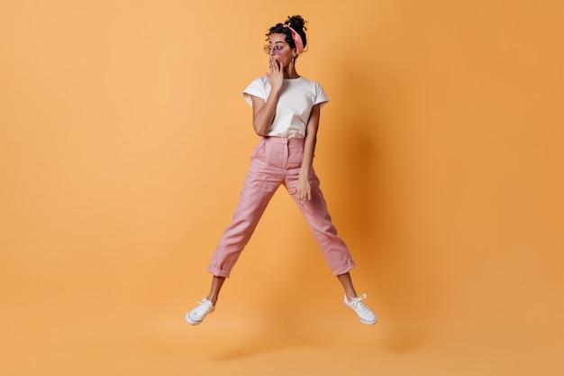 Zszokowana kobieta w różowych spodniach skacze i odwraca wzrok