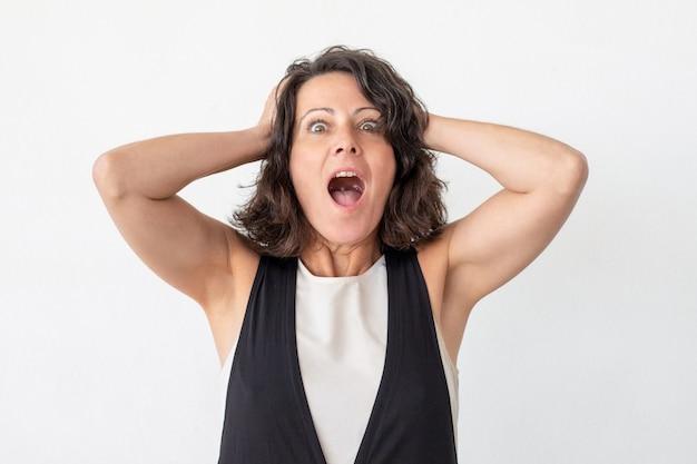 Zszokowana kobieta w średnim wieku krzyczy