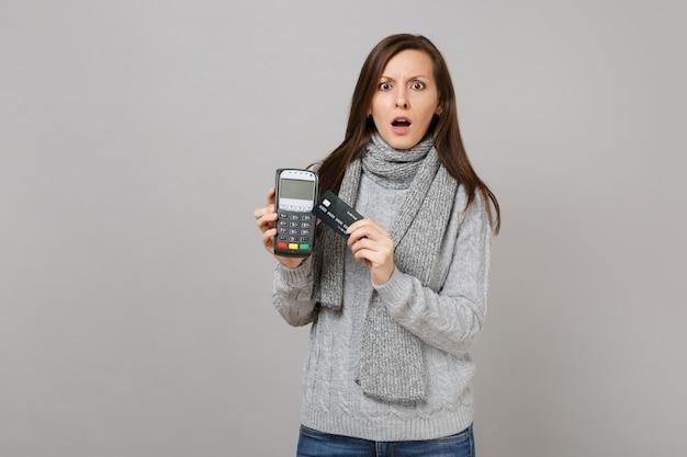 Zszokowana kobieta w swetrze szalik trzymać bezprzewodowy nowoczesny bankowy terminal płatniczy do przetwarzania, nabywania płatności kartą kredytową na białym tle na szarym tle. styl życia, szczere emocje ludzi, koncepcja zimnej pory roku.