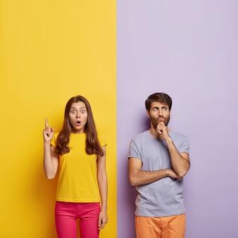 Zszokowana kobieta wskazuje w górę, trzyma usta otwarte, zamyślony nieogolony mężczyzna trzyma brodę