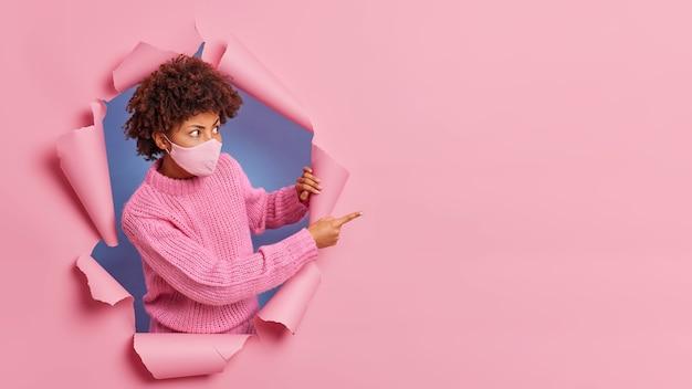 Zszokowana kobieta z kręconymi włosami patrzy podejrzliwie w papierową dziurkę i wskazuje miejsce na reklamę