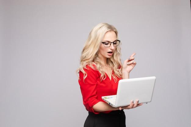 Zszokowana kobieta z otwartymi ustami prowadzenia komputera