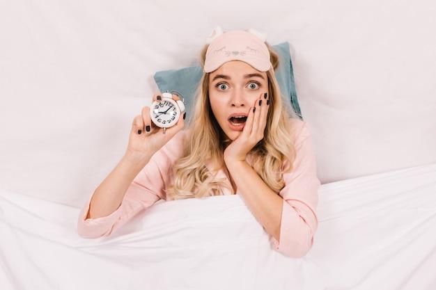 Zszokowana kobieta z zegarem pozuje z otwartymi ustami