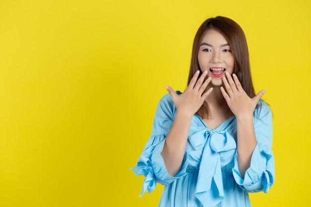 Zszokowana kobieta zakrywająca usta rękami na żółtej ścianie