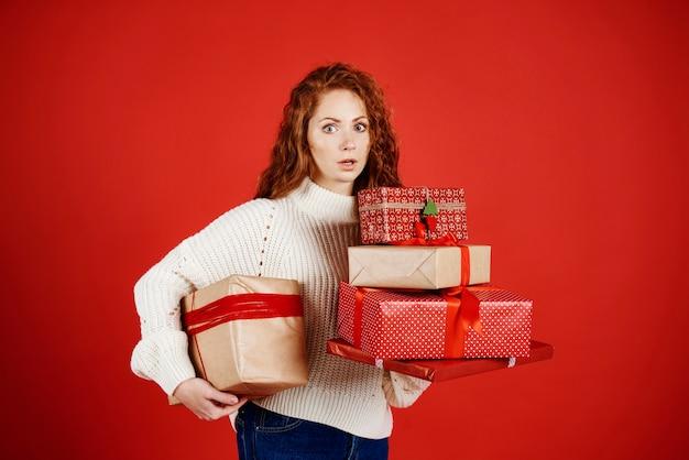 Zszokowana kobieta ze stosem prezentów świątecznych