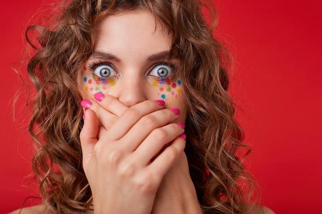 Zszokowana kręcona kobieta wygląda z szeroko otwartymi oczami, krzyżuje dłonie na ustach, wygląda na przestraszoną