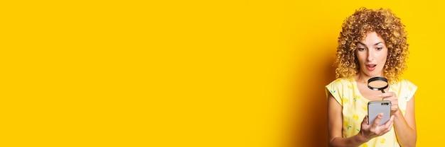 Zszokowana, kręcona młoda kobieta, patrząc przez lupę do telefonu na żółtej powierzchni