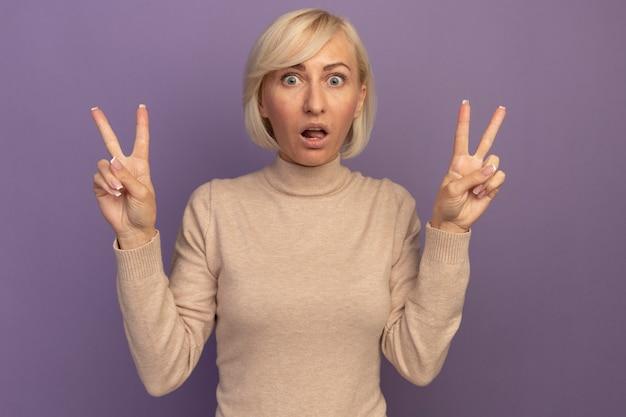 Zszokowana ładna blondynka słowiańska gestykuluje ręką znak zwycięstwa dwiema rękami na fioletowo