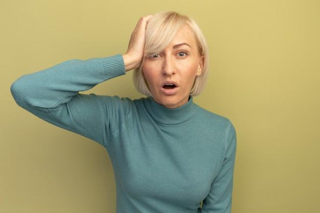 Zszokowana ładna blondynka słowiańska kobieta kładąc rękę na głowie na oliwkowej zieleni