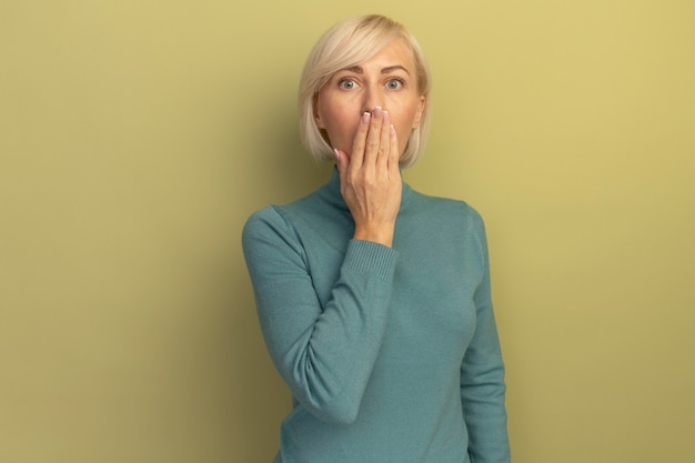 Zszokowana ładna blondynka słowiańska kobieta kładzie dłoń na ustach odizolowanych na oliwkowej ścianie