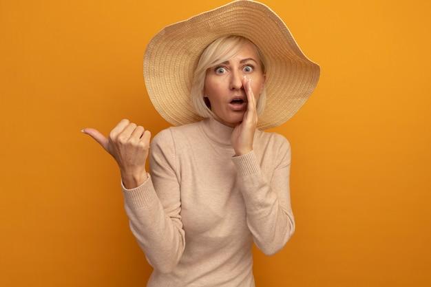 Zszokowana ładna blondynka słowiańska kobieta w kapeluszu plażowym trzyma rękę blisko ust i wskazuje na bok na pomarańczowo