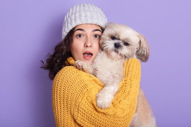 Zszokowana ładna dziewczyna trzyma psa i patrząc bezpośrednio na aparat z otwartymi ustami