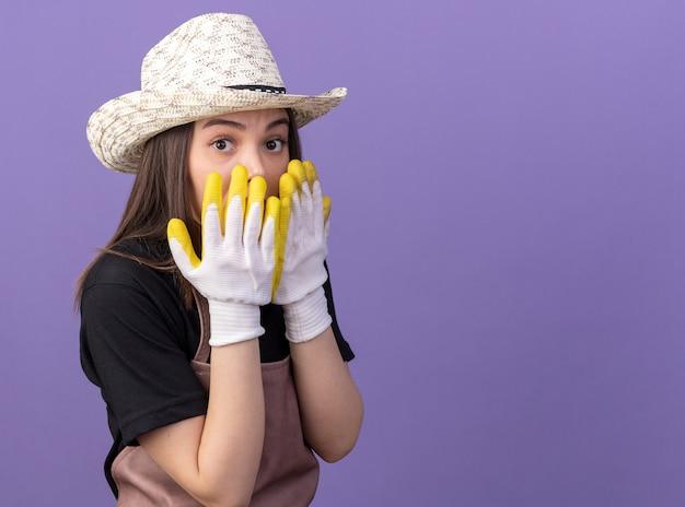 Zszokowana ładna kaukaska ogrodniczka w kapeluszu ogrodniczym i rękawiczkach kładzie ręce na ustach