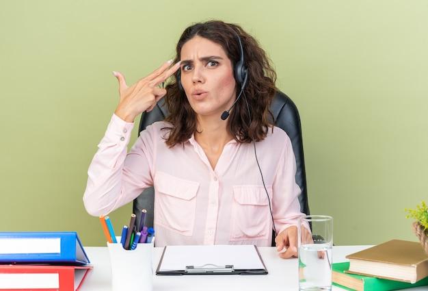 Zszokowana ładna kaukaska operatorka call center na słuchawkach siedząca przy biurku z narzędziami biurowymi trzymająca rękę przy jej świątyni, gestykulując znak pistoletu na zielonej ścianie