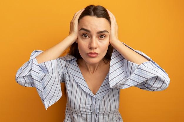 Zszokowana ładna kobieta trzyma głowę na białym tle na pomarańczowej ścianie