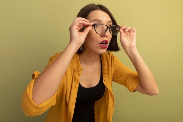 Zszokowana ładna kobieta trzyma i patrzy na bok przez okulary optyczne odizolowane na oliwkowej ścianie