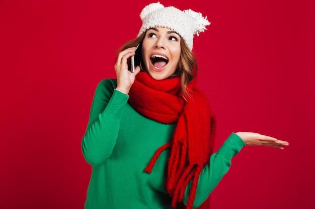 Zszokowana ładna młoda kobieta rozmawia przez telefon.