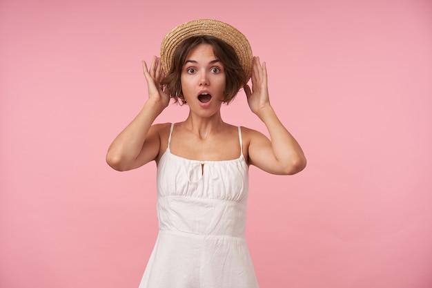 Zszokowana ładna młoda kobieta z krótkimi brązowymi włosami, ubrana w białą elegancką sukienkę z paskami i czapką, patrząc zdziwiona i unosząca brwi, odizolowana