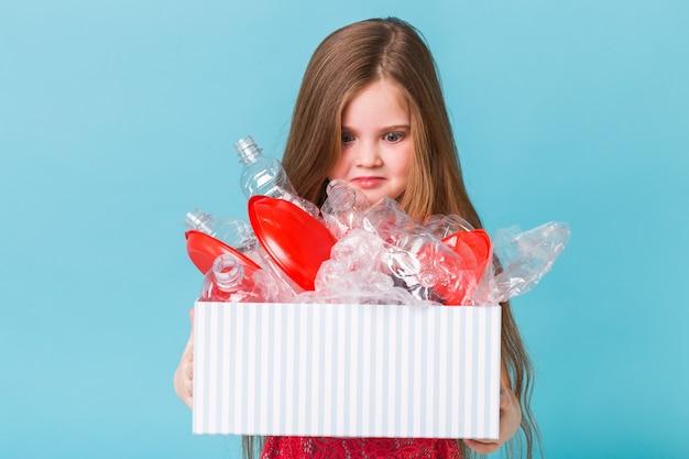 Zszokowana mała dziewczynka patrzy z otwartymi oczami i zmartwioną miną, trzymając pudełko z plastikowymi odpadami na niebieskiej ścianie.