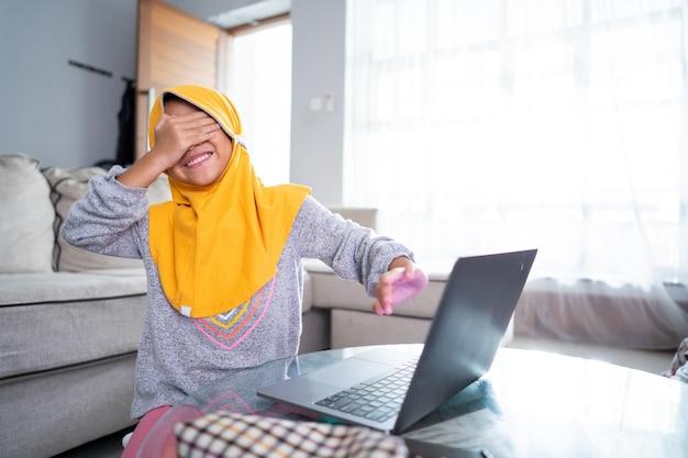 Zszokowana mała dziewczynka zakrywa oczy podczas korzystania z laptopa w domu