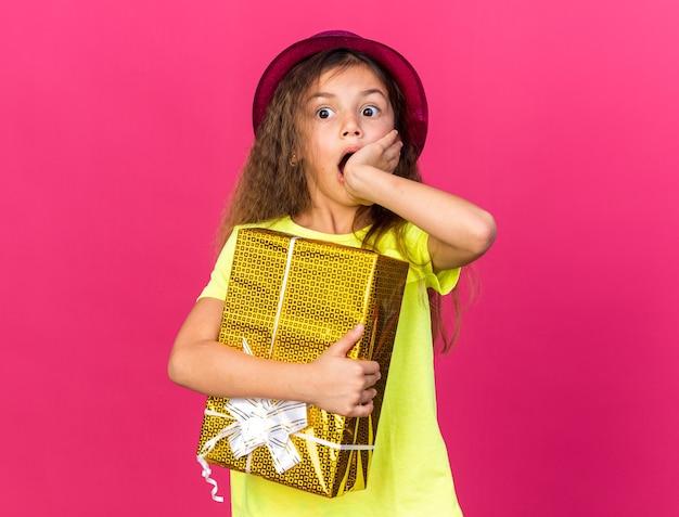 Zszokowana mała kaukaska dziewczynka w fioletowym kapeluszu imprezowym, kładąca dłoń na ustach i trzymająca pudełko na prezent na różowej ścianie z miejscem na kopię